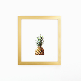 Pineapple art in clean gold frame on white wall