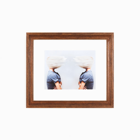 Classic warm wood frame with abstract hair photo on white wall