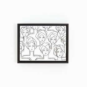 Black and white abstract faces art in black frame on white wall