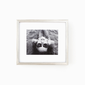 Silver frame with black and white photo of a girl in sunglasses on white wall