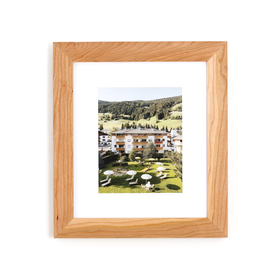 Framed cherry wood photo of landscape on white wall