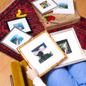 Woman with framed photos on lap and floor surrounding her