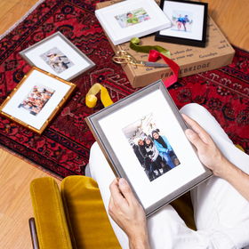 Woman holding framed photo of mom and kids in lap surrounded by framed photos on floor.